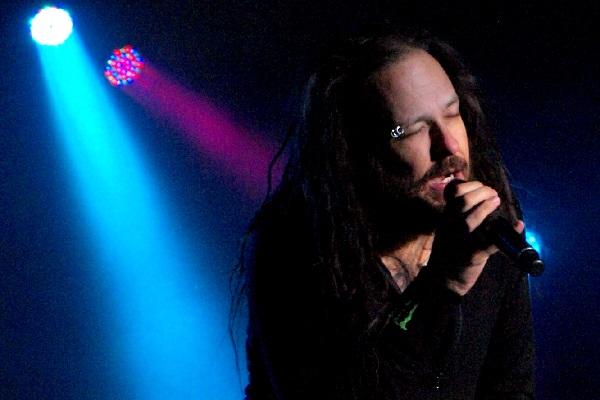 Jonathan Davis of Korn performing amid dark blue lighting.