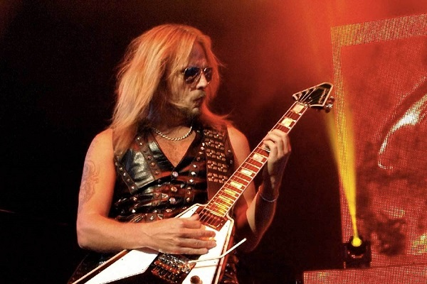 Photo of RIchie Faulkner of Judas Priest performing live amid red and yellow lighting.