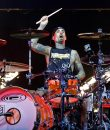 Travis Barker of Blink-182 performing live, rocking out on a red and white drum kit.
