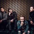 A photo of rock band Shinedown posing against a light brown background.