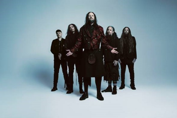 Photograph of nu-metal band Korn standing against a blue background.