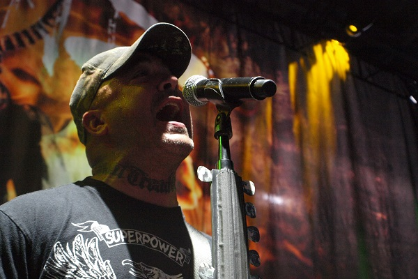 Aaron Lewis of Staind performing live amid yellow and orange lighting.