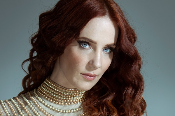 Epica vocalist Simone Simons posting with a beige collard shirt and bright, blue eyes. Epica's new album is 2021's