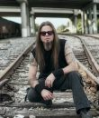 """Todd La Torre of Queensryche, posted on railroad tracks on a dark day. La Torre has a new solo album out, """"Rejoice in the Suffering."""""""