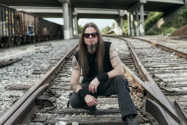 "Todd La Torre of Queensryche, posted on railroad tracks on a dark day. La Torre has a new solo album out, ""Rejoice in the Suffering."""
