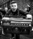 Dropkick Murphys pictured on a city street, in black and white.