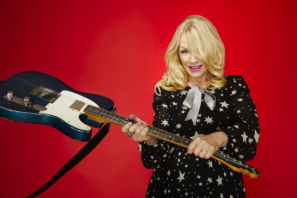 Nancy Wilson of heart slugging her electric guitar amid a bright red background.