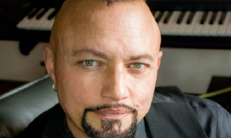 Geoff Tate sits in his studio in front of a grand piano.