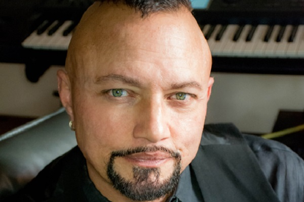 Geoff Tate sits in his studio in front of a black and white keyboard.