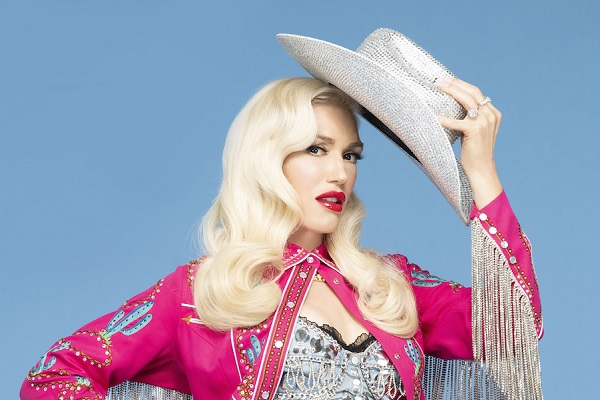 Gwen Stefani wearing a hot pink, Western-style shirt and holding a cowboy hat.