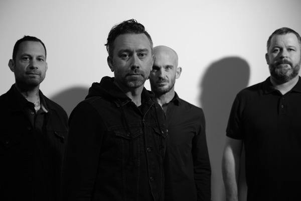 Rise Against pictured in black and white, featuring (from left to right) Joe Principe, Tim McIlrath, Zach Blair and Brandon Barnes.