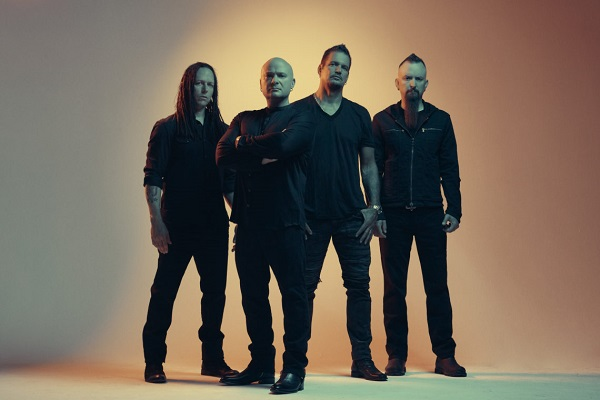 The members of Disturbed standing against a dimly lit background.