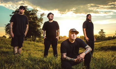 The members of P.O.D. stand outside in a green field in this press image.