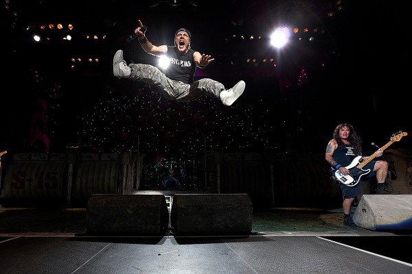 Bruce Dickinson of Iron Maiden jumping in the air during a live concert.
