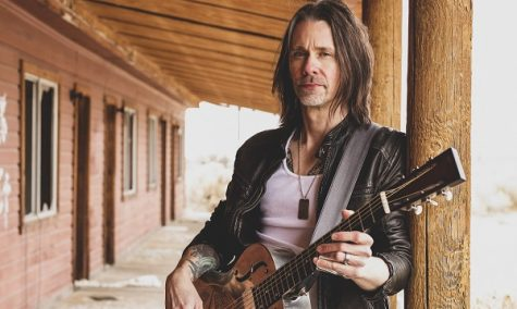 Myles Kennedy standing with an acoustic guitar.