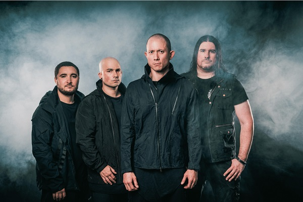 Trivium band photo, featuring the band standing amid a dark, smoky background.