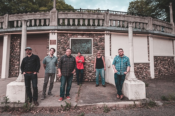 Lansing, Michigan, band Harborcoat stands for a press photo outside.