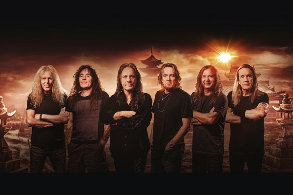 Metal band Iron Maiden standing amid a black and orange background.