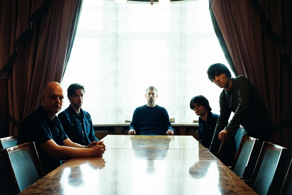 The members of Radiohead sitting at the end of a long table.