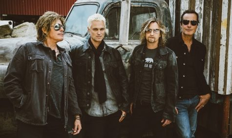 Photograph of Stone Temple Pilots standing in front of a classic car.