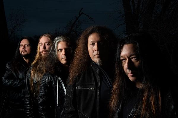 Promo photo of thrash metal band Testament standing amid a dark background.